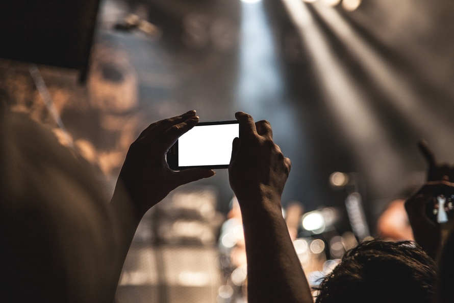 Concert photography being taken with a smartphone. The recent Apple patent to disable video recording at concerts has caught major buzz, where the Apple patent for texting and driving is not being heavily publicized. Photo by: pexels.com