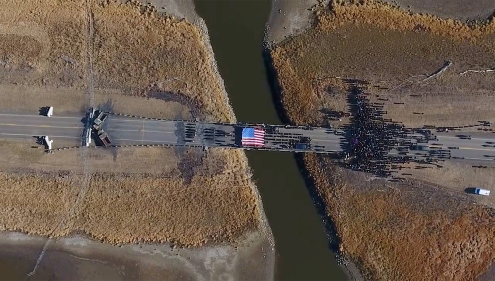 The Backwater Bridge on Highway 1806 over Cantapeda Creek. Water Protectors during a peaceful prayer ceremony in front of the police brigade. Image from the film AWAKE: A DREAM FROM STANDING ROCK captured by Myron Dewey