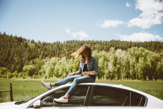 A female relaxing outside of a car. Photo by: Pexels.com