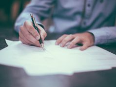 A person drafting a report. Photo by: Pexels.com
