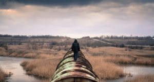 A person walking on a pipeline. Photo by: Pexels.com
