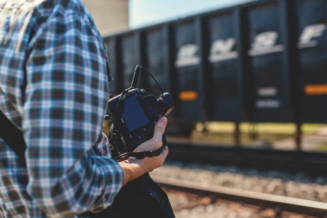 Photographer looking to capture a scene next to a train. Photo by: Pexels.com