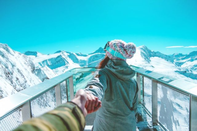 Two people taking a look over a mountain range. Photo by: Daniel Frank / Pexels.com