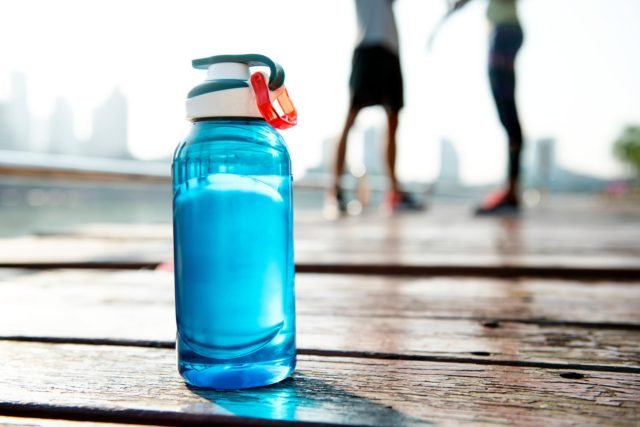 A water bottle with two runners in the background. Photo by: Pexels.com